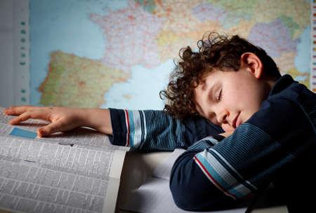 Boy sleeping while doing his homework photo