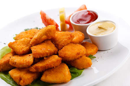Close up of nuggets with sauces on a white plate