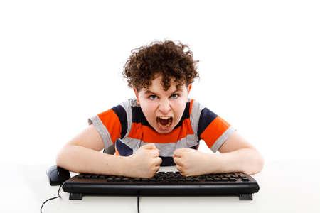 banging: Angry boy banging on the keyboard Stock Photo