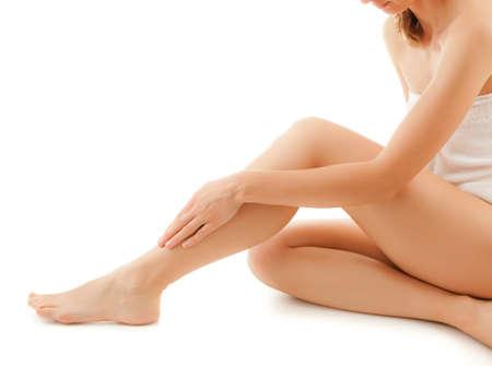 Frau massiert die Beine sitzt auf weißem Hintergrund