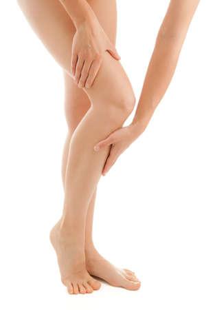 mujer celulitis: Mujer masajear las piernas de pie sobre fondo blanco Foto de archivo