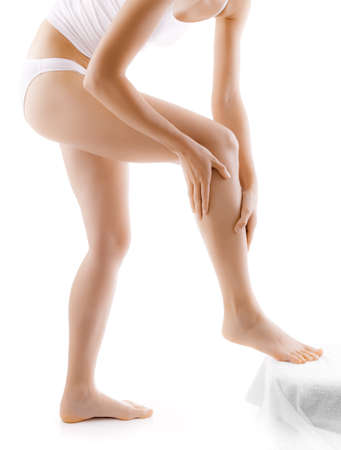 waxed legs: Woman massaging legs standing on white background