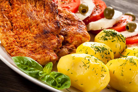 caprese salad: Fried pork chops, boiled potatoes and caprese salad