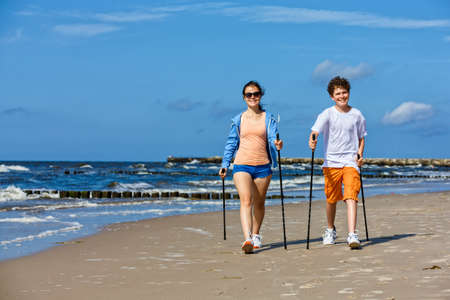 Nordic walking, young people working out on beach