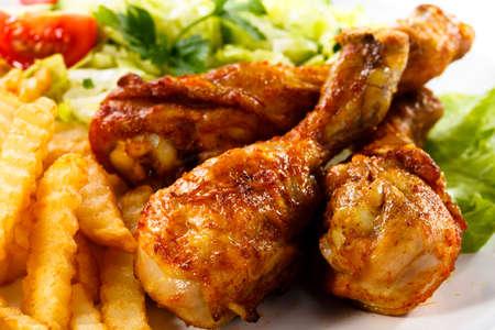 Gegrillte Hühnerbeine mit Pommes frites und Gemüse Lizenzfreie Bilder