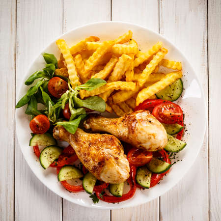 Grilled chicken drumsticks with chips and vegetables