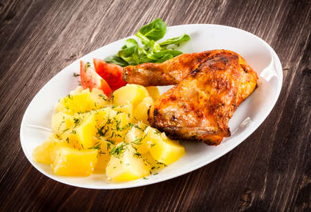 Barbecued chicken leg with boiled potatoes and vegetables Imagens