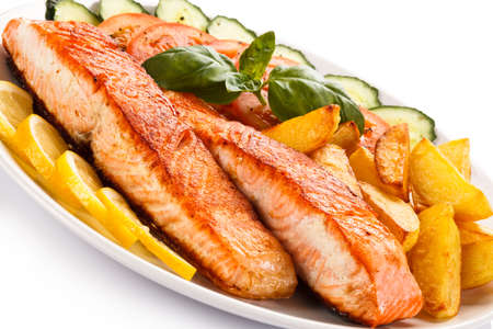 Grilled salmon and vegetables on white background photo