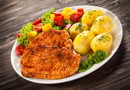 vegetable salad: Fried pork chops boiled potatoes and vegetable salad