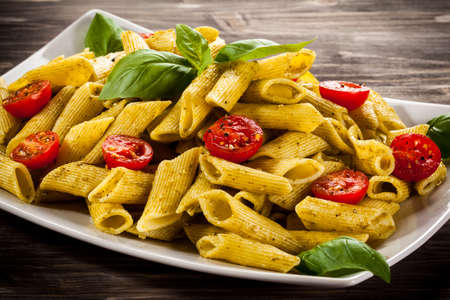 eating pasta: Pasta with pesto sauce and vegetables