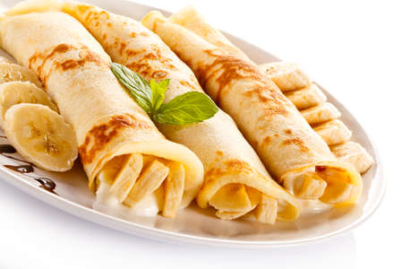 crepe: Crepes with bananas and cream on white background Stock Photo