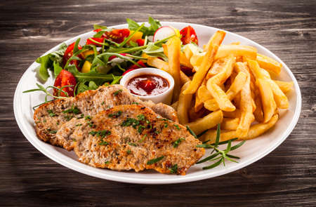 Fried steaks French fries and vegetables Imagens