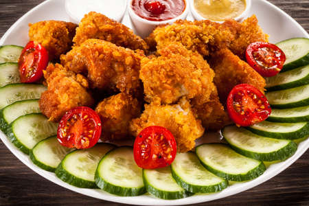 Fried chicken nuggets and vegetables photo