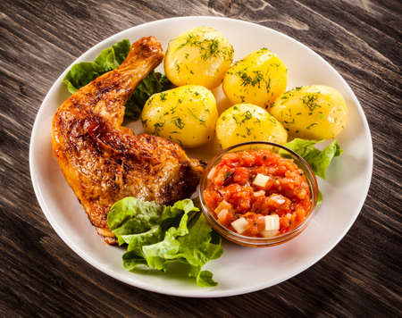 barbecued: Barbecued chicken legs with boiled potatoes and vegetables