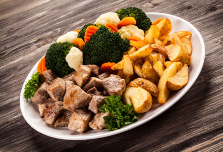 beef stew: Grilled meat with baked potatoes and vegetables Stock Photo