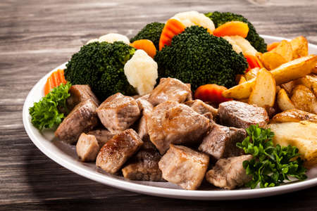 baked potatoes: Grilled meat with baked potatoes and vegetables Stock Photo