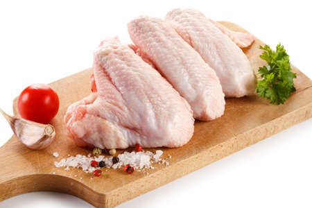 pollo: Raw chicken wings on cutting board