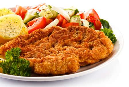 schnitzel: Fried pork chop, boiled potatoes and vegetable salad