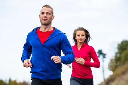 sport woman: Healthy lifestyle - woman and man running in park