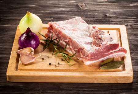 chops: Raw pork ribs on cutting board and vegetables Stock Photo