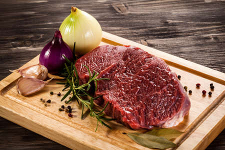 chops: Raw beef on cutting board and vegetables