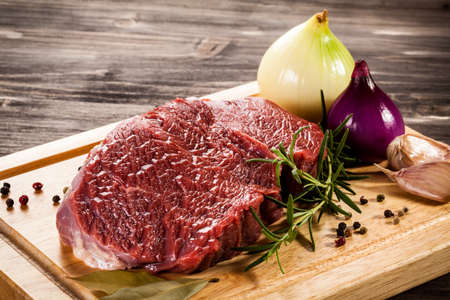 cebollas: Raw beef on cutting board and vegetables