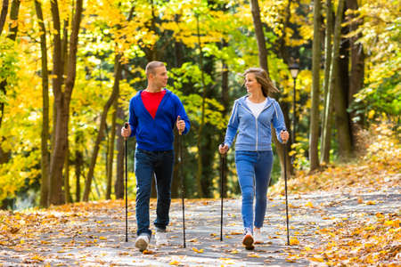 person walking: Nordic walking - active people working out outdoors