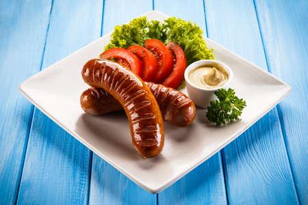 chorizos asados: embutidos y verduras a la parrilla Foto de archivo