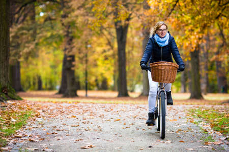 Urban biking - woman riding bike in city park Standard-Bild