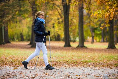 edad media: Nordic Walking - mujer de mediana edad que trabaja en el parque de la ciudad