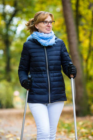 vecchiaia: Nordic Walking - donna di mezza età che lavora nel parco cittadino
