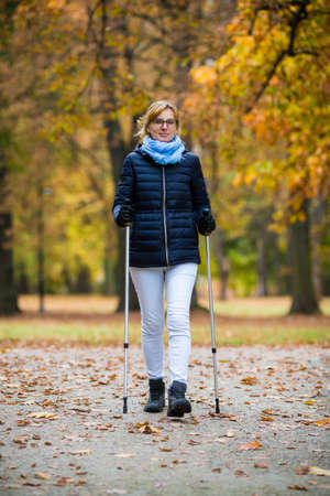 40 year old woman: Nordic Walking - middle-aged woman working out in city park