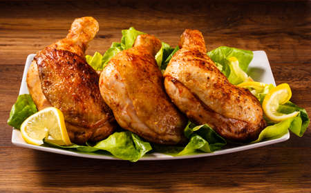 Roast chicken legs and vegetables Imagens