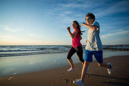 two children: Teenage girl and boy running, jumping on beach Stock Photo