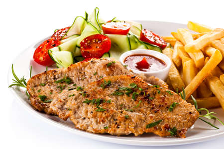 schnitzel: Grilled steak, French fries and vegetables on a white background Stock Photo