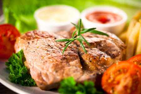 chops: Grilled steak, French fries and vegetables on a white background Stock Photo