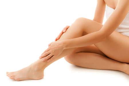 mujer celulitis: Mujer masajear las piernas que se sientan en un fondo blanco