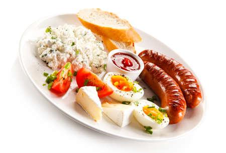 huevo blanco: Desayuno - huevo cocido, salchichas fritas, queso y verduras casa Foto de archivo