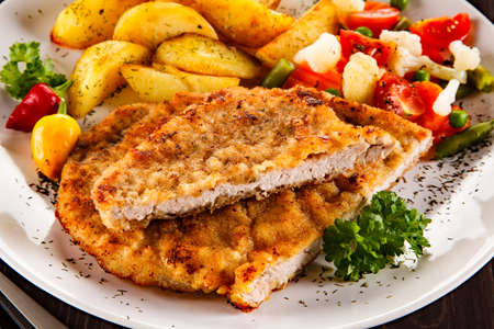 chops: Fried pork chop, baked potatoes and vegetable salad
