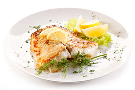Fish dish - fried fish fillet and vegetables Standard-Bild
