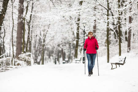 winter: Nordic Walking - middle-aged woman working out in city park