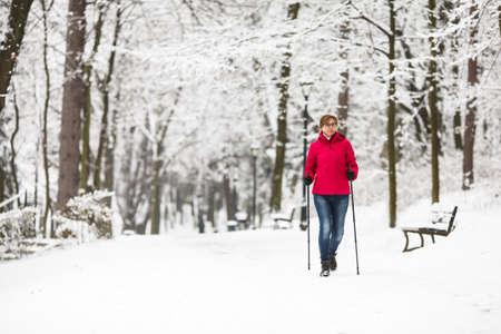 Nordic Walking - mujer de mediana edad que trabaja en el parque de la ciudad