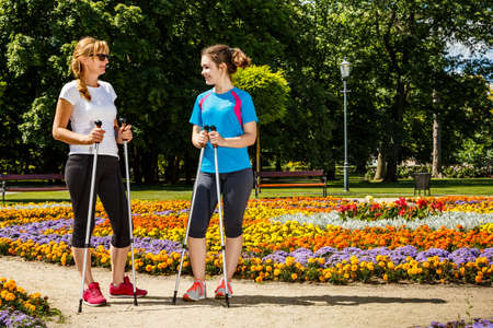 power walking: Nordic walking - active people working out in park