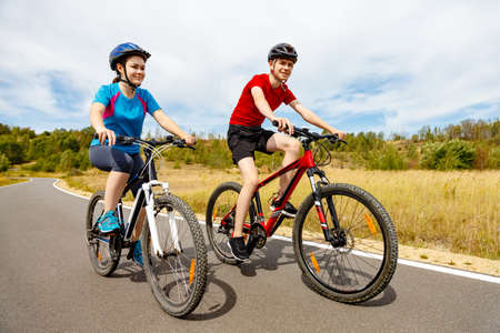 girl in sportswear: Healthy lifestyle - teenage girl and boy cycling