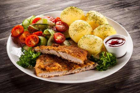 chops: Fried pork chops, baked potatoes and vegetable salad