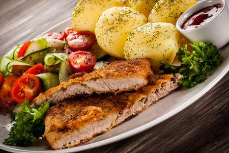 braciole di maiale fritte, patate al forno e insalata di verdure Archivio Fotografico