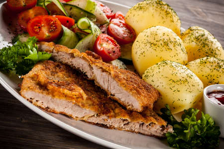 Fried pork chops, baked potatoes and vegetable salad
