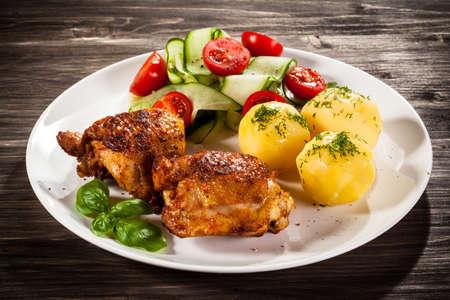 pollo a la plancha: muslos de pollo y verduras a la parrilla Foto de archivo