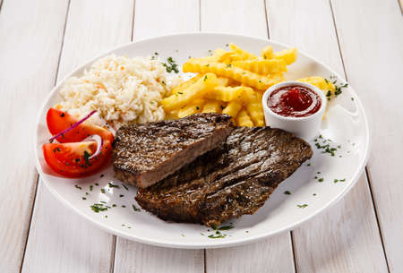 french fries plate: Grilled steaks, French fries and vegetables
