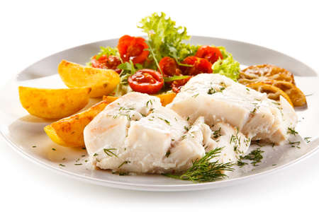 Fish dish - boiled fish fillet, baked potatoes and vegetables Standard-Bild